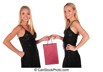 Twin girls holding small bag