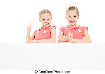 Twin girls look out from behind obstacles
