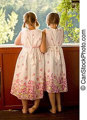Twin girls on porch in summer dresses