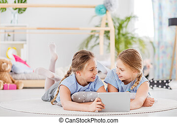 Twin girls sharing a tablet