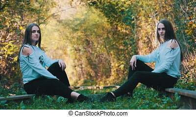Two Young Twin Girls Sit on the Train Tracks Opposite Each Other and Look at Camera in Green Nature Background. Beautiful Young pretty twin-sisters with long flowing hair. Gemini women. Slow Motion 4K