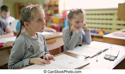 Twin girls sitting at a desk in a preschool class. Children at school are sitting at the tables.