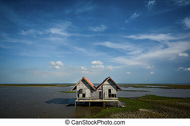 House with double gable roofs among lake landscape