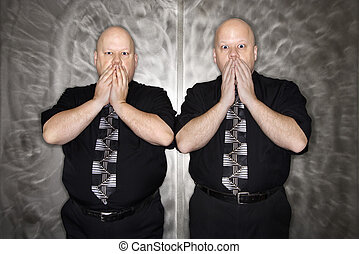 Twin men covering mouth.