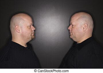 Twin men staring.