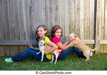 Twin sister girls playing smartphone and chihuahua dog -...