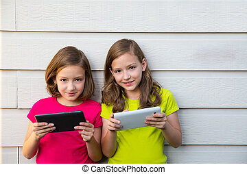 Twin sister girls playing with tablet pc happy on white wall