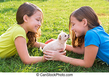 twin sister kid girls and puppy dog lying in lawn - twin ...