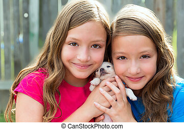 Twin sisters and puppy pet dog chihuahua playing together...