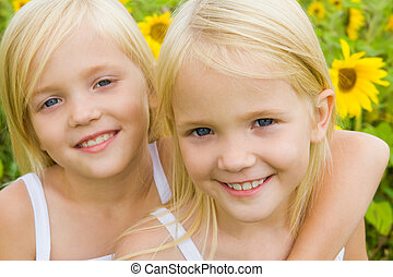 Twin sisters - Portrait of cute girl embracing her twin...