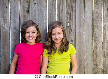 Twin sisters with different hairstyle posing on wood fence