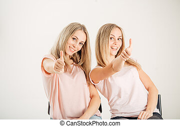 Twin sisters with thumbs up on white