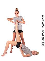 Twin sport girls. holding lying sister\'s leg