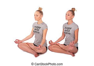 Twin sport girls meditating half-turned