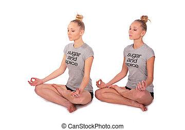 Twin sport girls meditating half-turned