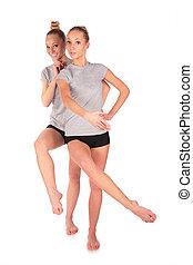 Twin sport girls posing balancing