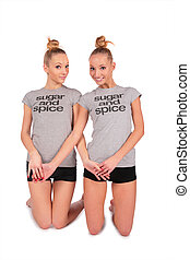 Twin sport girls stands on knees