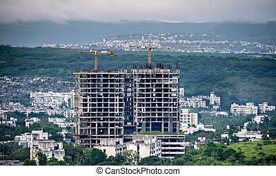 Twin, tall buildings under construction in Pune, Maharashtra, India.