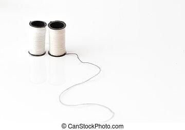 twin white thread loom standing on black thread over white bakcground