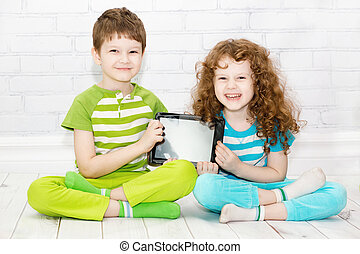 Twins boy and girls with the tablet PC on a light background.