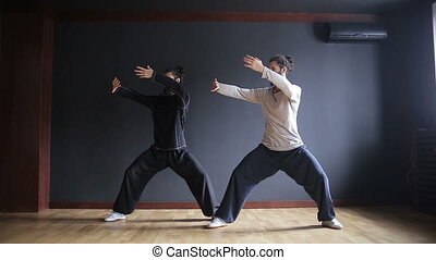 Twins brothers practice Tai Chi in the training hall.