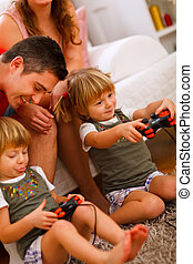 Twins daughters playing on console at home