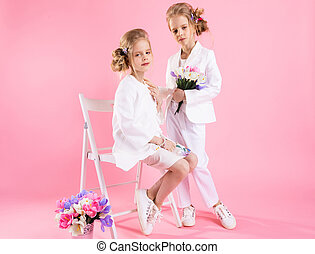Twins girls in light clothes with bouquets of flowers posing near a chair on a pink background.