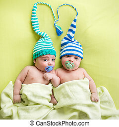 Twins infant brothers babies weared in striped hats tied by heart.