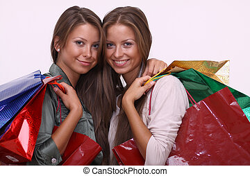 Twins sisters holding shopping bags