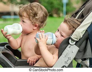 twins suck a bottle with milk