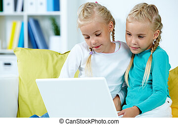 Twins with laptop - Portrait of twin girls studying in front...