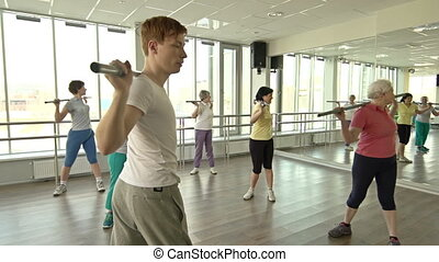 Twirling - Male fitness professional instructing female...