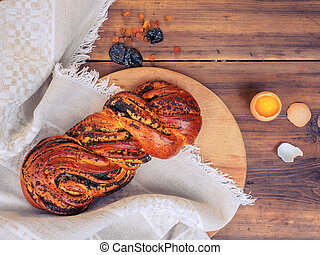 Twisted loaf with poppy seeds and chicken egg with yolk and broken shells on a background of rough cloth and old table from the boards. Raisins and prunes, sweet bun. Still life in rustic style