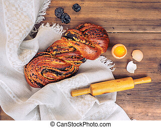 Twisted loaf with poppy seeds and chicken egg with yolk and broken shells, wooden rolling pin on a background of rough cloth and old table from the boards. Still life in rustic style