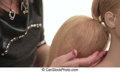 Barber works with long hair mannequin, master was formed the mannequin volumetric balloon of the hair and is covering him a strand of hair that gently distributes, close up