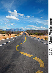 Twisting lane marking on road in desert