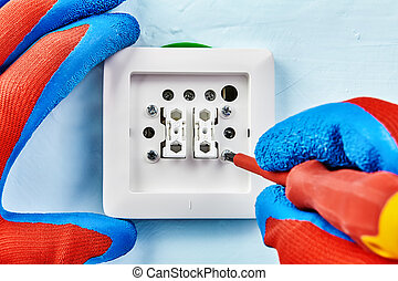 Twisting screw in light switch by insulated screwdriver. - ...