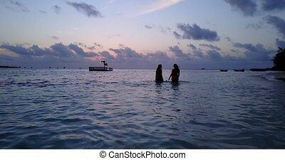 Two 2 beautiful young girls at sunset sunrise splashing on the beach in evening with water and sand
