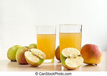 two 2 glasses of juice, Apple juice, whole apples and apples cut in half