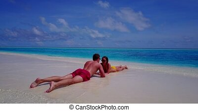 two 2 people laying romantic young couple sunbathing on a...