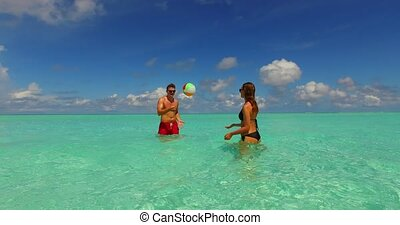 two 2 people playing ball romantic young couple on a tropical island of white sand beach and blue sky and sea