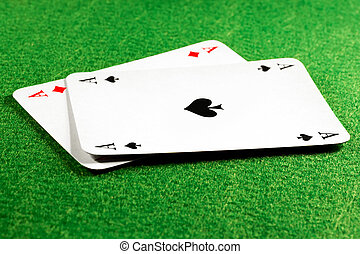Two aces on green felt casino table