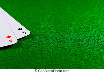 Two aces on the green felt casino table.