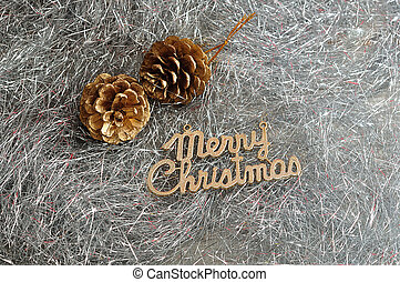 Two acorns with merry Christmas isolated on silver tinsel