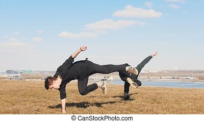 Two acrobatic men training their skills outside. Mid shot