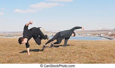 Two acrobatic men training their tricking skills outside....