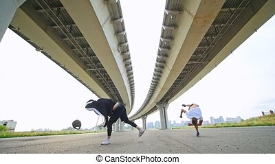 Two acrobats doing flips under the bridge