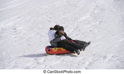 two active happy kids boy and girl riding tube on snow in winter with emotions