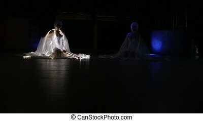 two beautiful actress girl in white clothes and unusual white wigs dancing with LED wings that glow on the stage under the floodlights at night