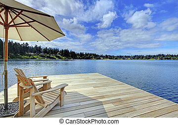 Two adirondack wooden chairs with umbrella on dock facing blue lake.